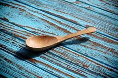 Cucchiaio di legno su ciano colore del bordo di legno Fotografie Stock Libere da Diritti