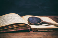 Cucchiaio di legno su un libro d'annata fotografia stock libera da diritti