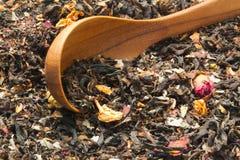 Cucchiaio di legno sul mucchio del tè e del fiore asciutti della foglia Fotografia Stock