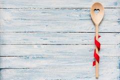 Cucchiaio di mescolatura di legno su un fondo blu-chiaro fotografie stock