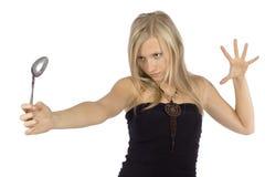 Cucchiaio di piegamento della donna con la forza di mente Immagine Stock