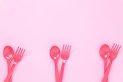 Cucchiaio di plastica variopinto e forchetta sul backgroun rosa della tavola Immagini Stock Libere da Diritti