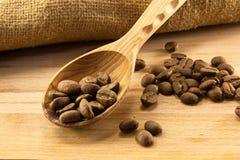 Cucchiaio e caffè di legno a bordo Fotografia Stock