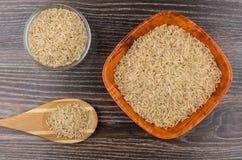 Cucchiaio e ciotole di legno con riso sbramato sulla tavola scura Immagini Stock Libere da Diritti