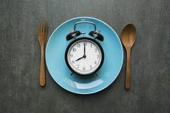 Cucchiaio e forchetta dell'orologio dell'alimento sulla tavola Fotografia Stock
