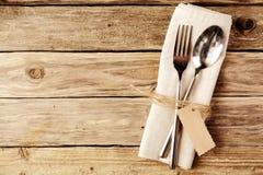 Cucchiaio e forchetta legati sul tovagliolo bianco con l'etichetta Fotografia Stock Libera da Diritti