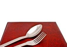 Cucchiaio e forchetta sul coperchio del menu fotografie stock