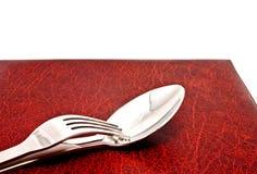 Cucchiaio e forchetta sul coperchio del menu fotografie stock libere da diritti