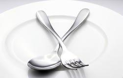Cucchiaio e forchetta sul piatto bianco Fotografia Stock