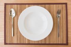 Cucchiaio e forchetta vuoti del piatto sulla stuoia Immagine Stock Libera da Diritti