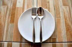 Cucchiaio e forchetta vuoti del piatto sulla tavola Fotografie Stock