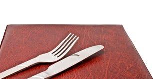 Cucchiaio e lama sul coperchio del menu fotografie stock