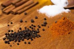 Cucchiaio e mucchio delle spezie sulla tavola Immagine Stock