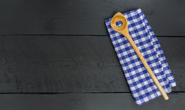 Cucchiaio e panno di legno del piatto su fondo di legno nero fotografia stock