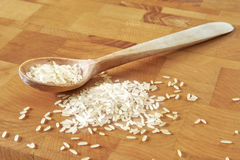 Cucchiaio e riso di legno sul tagliere Fotografia Stock Libera da Diritti