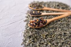 Cucchiaio e tipi differenti di tè asciutti sulla tavola immagine stock libera da diritti