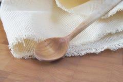 Cucchiaio e tovagliolo di legno sul tagliere Immagini Stock