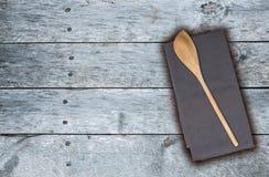 Cucchiaio ed asciugamano di cucina di legno su legno d'annata grigio Immagine Stock