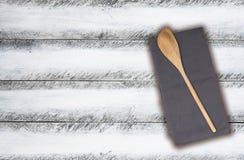 Cucchiaio ed asciugamano di cucina di legno su eleganza misera bianca Fotografie Stock