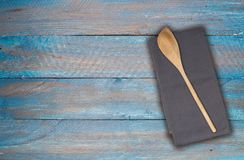 Cucchiaio ed asciugamano di cucina di legno su fondo di legno blu-grigio Immagine Stock Libera da Diritti