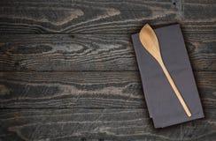 Cucchiaio ed asciugamano di cucina di legno su legno marrone Fotografie Stock Libere da Diritti