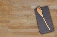 Cucchiaio ed asciugamano di cucina di legno sul bordo di legno usato Fotografia Stock Libera da Diritti