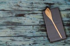 Cucchiaio ed asciugamano di cucina di legno sul legno dell'annata del turchese Fotografia Stock Libera da Diritti