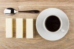 Cucchiaio, fila dei bastoni della caramella gommosa e molle e tazza di caffè nero Fotografie Stock Libere da Diritti