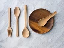 Cucchiaio, forchetta e piatto di legno su marmo bianco Immagine Stock