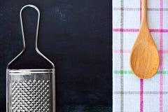 Cucchiaio, grattugia del metallo e tovaglia di legno Fotografia Stock