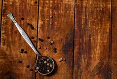 Cucchiaio metallico con pepe sulla tavola di legno, primo piano Fotografie Stock