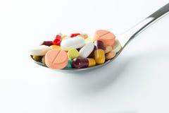 Cucchiaio in pieno delle pillole della medicina Immagini Stock