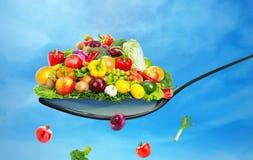 Cucchiaio in pieno di varie frutta e verdure Fotografia Stock