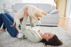 Cucciolo di sollevamento della donna mentre trovandosi sulla coperta Fotografia Stock