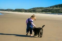 Cucciolo e bambino sulla spiaggia immagini stock libere da diritti