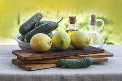 Cuccumbers and lemons. Cucumbers and lampns on wooden board with olive oil in the back Royalty Free Stock Photography
