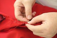 Cucendo a mano, ripari a mano l'abbigliamento fotografia stock libera da diritti