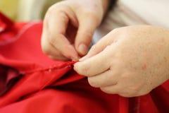 Cucendo a mano, ripari a mano l'abbigliamento fotografie stock libere da diritti