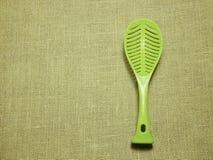 Cucharón plástica verde en fondo tejido harpillera Foto de archivo libre de regalías