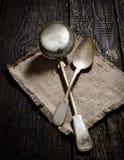 Cucharón y cuchara de sopa del vintage en una servilleta en un fondo de madera oscuro Foto de archivo libre de regalías