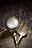 Cucharón y cuchara de sopa del vintage en una servilleta en un fondo de madera oscuro Fotos de archivo libres de regalías