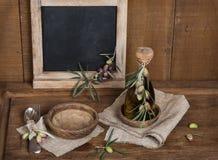 Cuchara, bifurcación y aceitunas y aceite de oliva, pizarra negra del menú encendido Imagenes de archivo