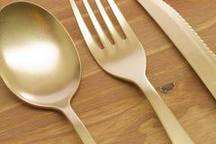 Cuchara, bifurcación y cuchillo de oro Foto de archivo libre de regalías