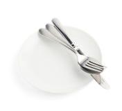 Cuchara, bifurcación y cuchillo sobre la placa blanca Imagen de archivo