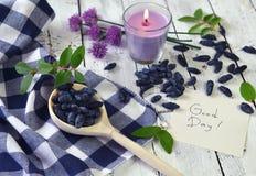 Cuchara con honeyberry, nota con el texto del buen día y vela Fotos de archivo libres de regalías