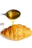 Cuchara con la miel y el croissant Fotos de archivo libres de regalías
