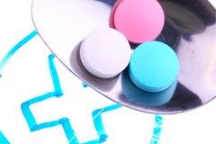 Cuchara con las píldoras en un fondo de la cruz médica Fotos de archivo libres de regalías