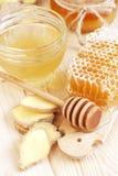 Cuchara con un descenso de colada de la miel de oro en el peine de la miel Fotos de archivo