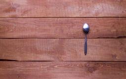 Cuchara de acero en una tabla de madera Imagenes de archivo