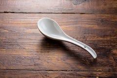 Cuchara de cerámica en la sobremesa de madera Fotos de archivo